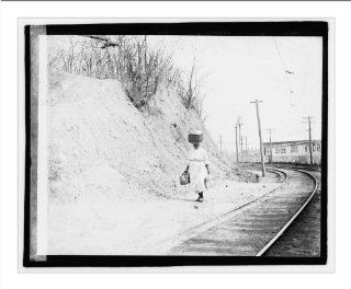 Historic Print (L): [African American woman with basket on head walking near railroad tracks]