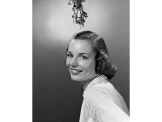 Studio portrait of young woman smiling with mistletoe hanging over her head Poster Print (18 x 24)
