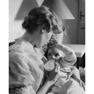 Young woman feeding her baby with a baby bottle Poster Print (18 x 24)